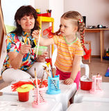 Bambino con le vernici di tiraggio dell'insegnante nella stanza del gioco. Immagini Stock