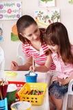 Bambino con le vernici di tiraggio dell'insegnante nella stanza del gioco. fotografia stock libera da diritti