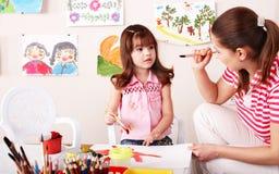 Bambino con le vernici di tiraggio dell'insegnante nella stanza del gioco. fotografie stock libere da diritti