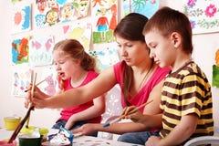 Bambino con le vernici di tiraggio dell'insegnante nella stanza del gioco. immagine stock libera da diritti