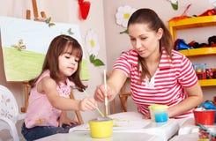 Bambino con le vernici di tiraggio dell'insegnante nella stanza del gioco. Fotografia Stock