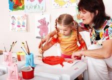 Bambino con le vernici di tiraggio dell'insegnante in playroom. immagini stock libere da diritti