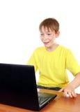 Bambino con un computer portatile Immagini Stock Libere da Diritti