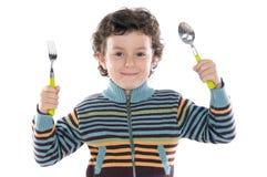 Bambino con un cucchiaio e una forchetta fotografia stock libera da diritti