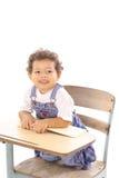 Bambino con un libro che si siede in scrittorio Fotografia Stock