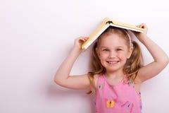 Bambino con un libro sulla sua testa Fotografia Stock