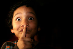 Bambino con un segreto o un'espressione di silenzio Fotografia Stock