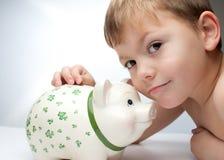 Bambino con una banca piggy Immagine Stock Libera da Diritti