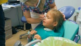 Bambino con una madre ad una ricezione del ` s del dentista La ragazza si trova nella sedia, dietro sua madre Il medico lavora co Immagini Stock Libere da Diritti