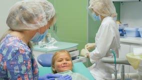 Bambino con una madre ad una ricezione del ` s del dentista La ragazza si trova nella sedia, dietro sua madre Il medico lavora co Fotografia Stock