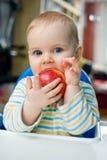 Bambino con una mela a casa; verticale Immagine Stock