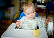 Bambino con una mela a casa; verticale Fotografia Stock