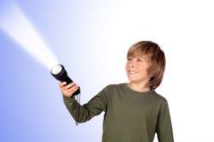 Bambino con una torcia elettrica che cerca qualcosa Immagini Stock Libere da Diritti