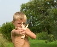 Bambino con uno slingshot. Fotografie Stock