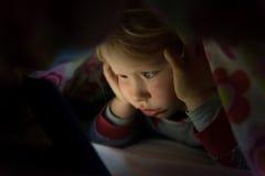 Bambino in coperta che fissa allo schermo d'ardore della compressa Immagini Stock Libere da Diritti