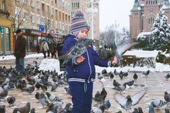 Bambino coperto di colombe mentre l'altra gente passa nei precedenti immagini stock