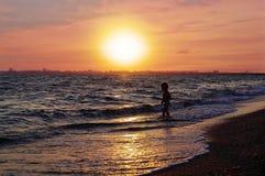 Bambino corrente sulla spiaggia su un bello tramonto rosso immagine stock