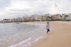 Bambino corrente sulla spiaggia Vista stupefacente sulla spiaggia e sul mare Blanes, Costa Brava, Catalogna, Spagna fotografia stock libera da diritti