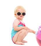 Bambino in costume da bagno ed occhiali da sole che giocano con la sfera Fotografia Stock Libera da Diritti