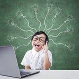 Bambino creativo con il computer portatile e la lampada di ramificazione Immagini Stock Libere da Diritti