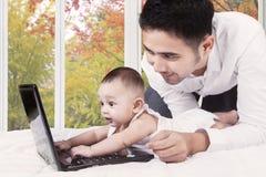 Bambino curioso con il papà che gioca computer portatile Fotografie Stock