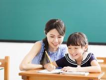 Bambino d'aiuto del giovane insegnante con la lezione di scrittura Fotografia Stock