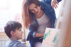 Bambino d'aiuto dell'artista femminile pensieroso alla classe della pittura Fotografia Stock Libera da Diritti