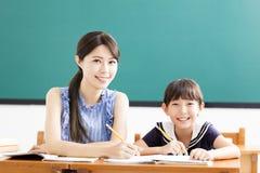 Bambino d'aiuto dell'insegnante con la lezione di scrittura Fotografia Stock
