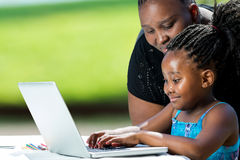 Bambino d'aiuto della madre africana sul computer portatile Fotografie Stock Libere da Diritti