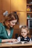Bambino d'aiuto della madre dopo la scuola bambino in età prescolare che fa compito con aiuto dell'istitutore concetto d'istruzio Fotografia Stock