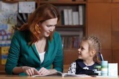 Bambino d'aiuto della madre dopo la scuola bambino in età prescolare che fa compito con aiuto dell'istitutore concetto d'istruzio Fotografie Stock
