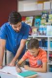 Bambino d'aiuto della scuola dell'insegnante con il suo compito in biblioteca Immagini Stock