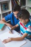 Bambino d'aiuto della scuola dell'insegnante con il suo compito in biblioteca Fotografie Stock Libere da Diritti