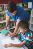 Bambino d'aiuto della scuola dell'insegnante con il suo compito in biblioteca Fotografia Stock