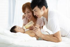 bambino d'alimentazione del padre e madre dalla bottiglia immagine stock libera da diritti