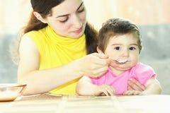 Bambino d'alimentazione della madre Fotografia Stock