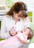 Bambino d'alimentazione della madre con il biberon in cucina Immagini Stock Libere da Diritti