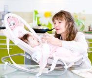 Bambino d'alimentazione della madre con il biberon in cucina Fotografia Stock