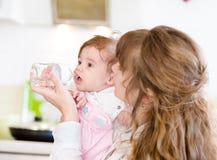 Bambino d'alimentazione della madre con il biberon in cucina Fotografia Stock Libera da Diritti