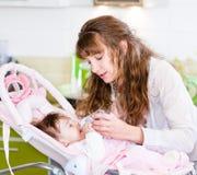 Bambino d'alimentazione della madre con il biberon in cucina Immagini Stock