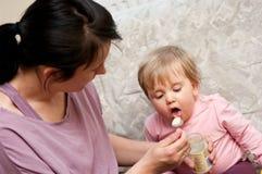 Bambino d'alimentazione della madre con il cucchiaio Fotografia Stock Libera da Diritti
