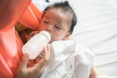 Bambino d'alimentazione della madre con la bottiglia per il latte immagini stock libere da diritti