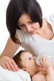Bambino d'alimentazione della madre dalla bottiglia Fotografie Stock Libere da Diritti