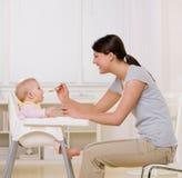 Bambino d'alimentazione della madre in highchair in cucina Fotografia Stock