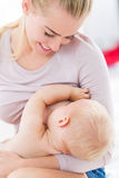 Bambino d'allattamento al seno della madre Immagine Stock