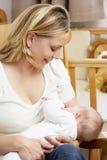 Bambino d'allattamento al seno della madre in scuola materna Fotografia Stock