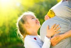 Bambino d'ascolto del piccolo bambino in pancia di sua madre all'aperto in natura soleggiata Madre incinta felice con la sua picc Fotografie Stock Libere da Diritti