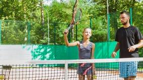 Bambino d'istruzione della vettura o dell'istruttore come giocar a tennise su una corte dell'interno video d archivio
