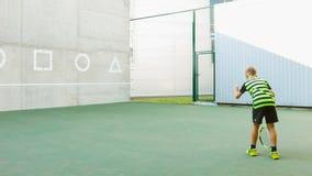 Bambino d'istruzione della vettura o dell'istruttore come giocar a tennise uso la parete per prepararsi video d archivio