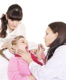 Bambino degli esami del medico con la gola irritata. fotografia stock